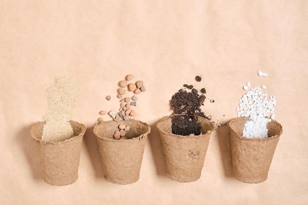 Plusieurs pots de tourbe avec différents ingrédients pour préparer un sol fertile pour les plantes, des pierres pour le drainage, de la perlite, de la terre pour les semis, de l'engrais pour le jardin