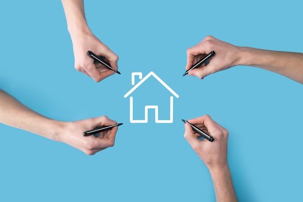 Plusieurs, quatre mains dessiner une icône de la maison avec un marqueur.concept immobilier.concept d'assurance et de sécurité des biens.innovation technologie internet concept de réseau.