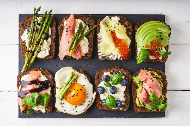Plusieurs sandwichs sains avec différentes garnitures. poisson, caviar, avocat, asperges, concombre, herbes, graines de sésame, pain sans gluten servi sur un plateau noir