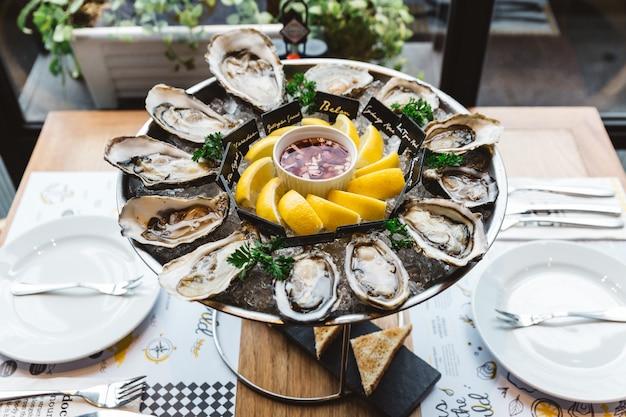 Plusieurs sortes d'huîtres fraîches servies dans un plateau rond avec une tranche de citron et une sauce épicée.