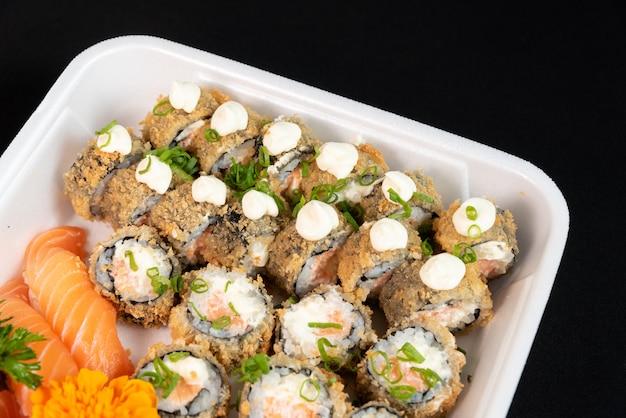 Plusieurs sushis à l'intérieur du récipient en polystyrène sur fond noir