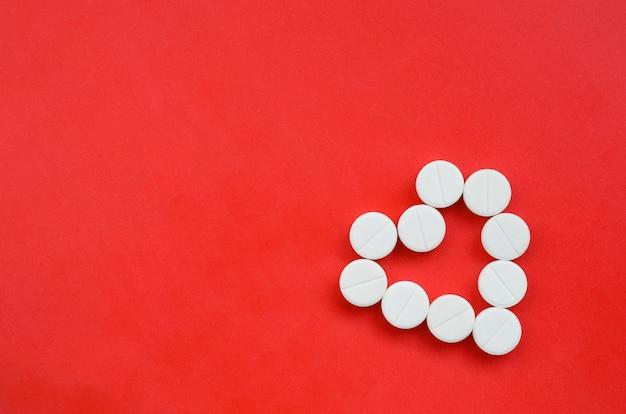 Plusieurs tablettes blanches reposent sur un fond rouge vif en forme de cœur