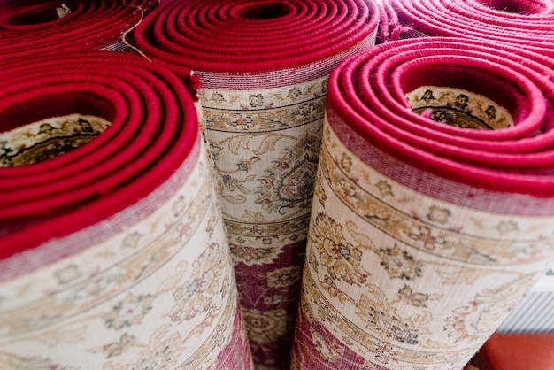 Plusieurs tapis dans une mosquée roulé debout pour le nettoyage