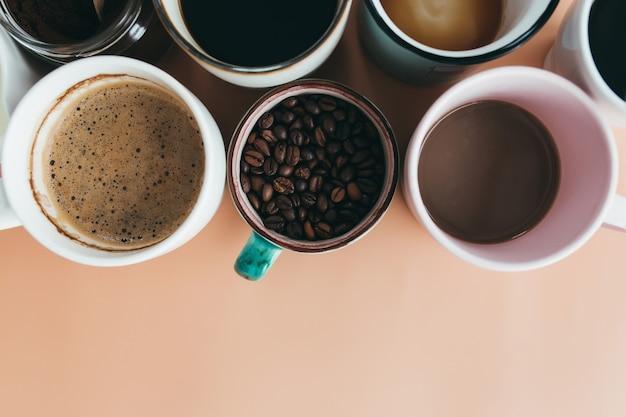 Plusieurs tasses à café, lait, haricots et café moulu en pot sur fond beige. photo de haute qualité