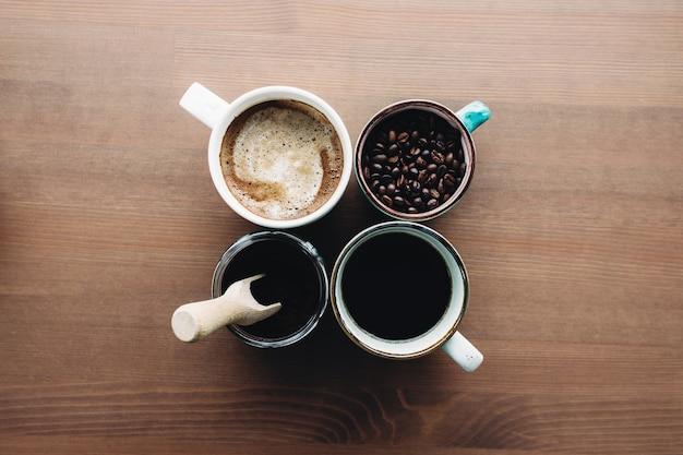 Plusieurs tasses à café, lait, haricots et café moulu en pot sur fond en bois. photo de haute qualité