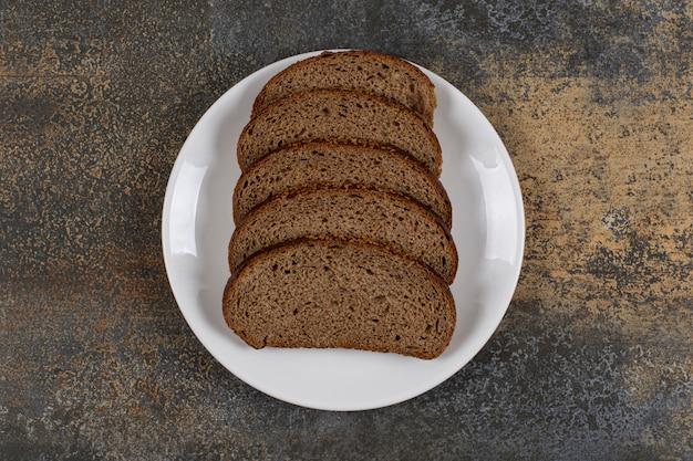 Plusieurs tranches de pain de seigle sur plaque blanche