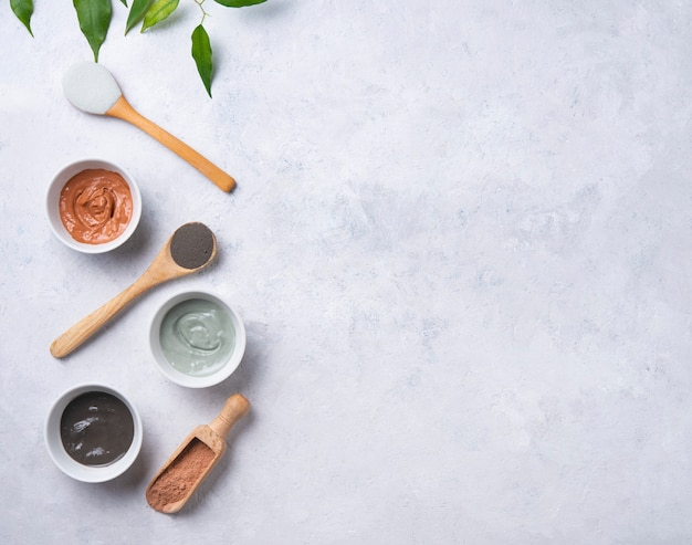 Plusieurs types d'argile cosmétique rose, vert et gris sur fond gris béton