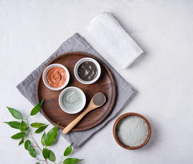 Plusieurs types d'argile cosmétique rose, verte et grise à la lavande sur un fond de béton gris