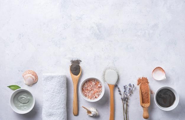 Plusieurs types d'argile cosmétique vert et gris avec du sel de mer rose et de la lavande sur un fond de béton gris