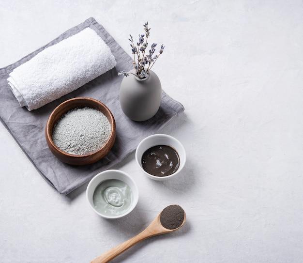 Plusieurs types d'argile cosmétique verte et grise à la lavande sur un fond de béton gris