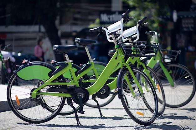 Plusieurs vélos verts dans la rue. vélos à louer