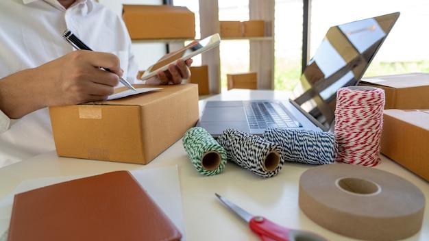 Pme entrepreneur de petite entreprise, jeune homme asiatique travaillant avec un ordinateur portable et une boîte d'emballage de livraison