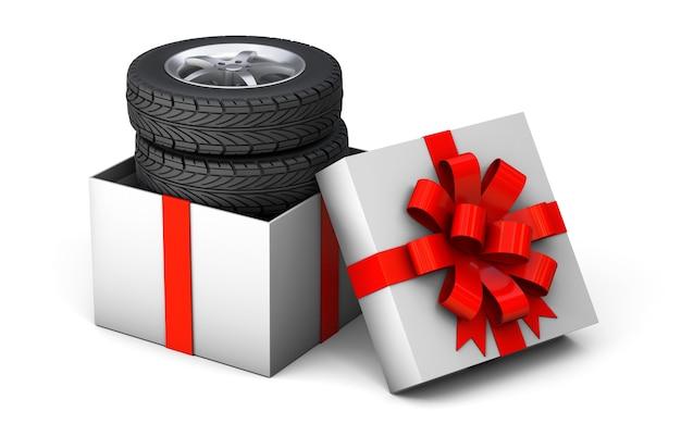 Pneu en cadeau un ensemble de quatre pneus dans une boîte cadeau attachée avec un ruban cadeau rouge avec un arc isolé