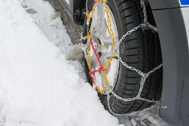 Pneu avec des chaînes à neige montées en hiver, jour de neige