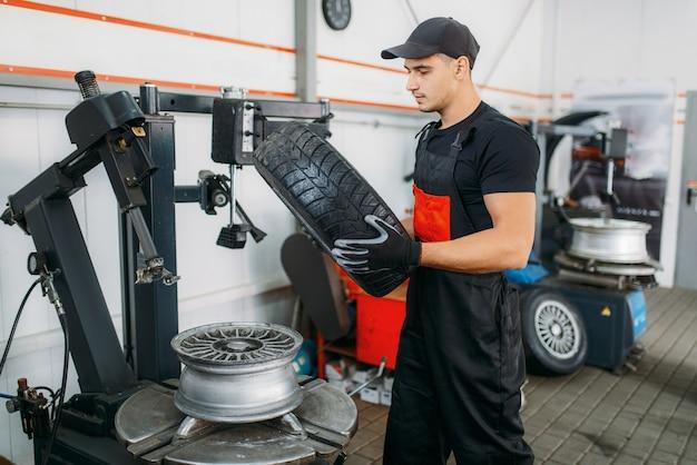 Pneu de changement de mécanicien, service de réparation. l'homme répare les pneus de voiture dans le garage, l'inspection automobile professionnelle en atelier