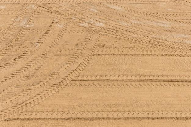 Le pneu du tracteur trace sur le sable après le nettoyage.