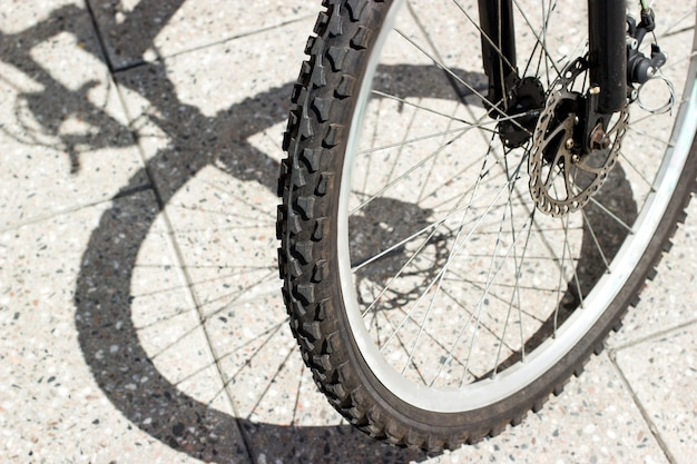 Pneu de roue avant de vélo et silhouette d'ombre sur la surface des carreaux de béton urbain