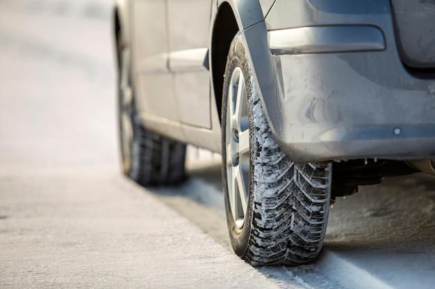 Pneu de voiture garé sur une route enneigée le jour de l'hiver. concept de transport et de sécurité.