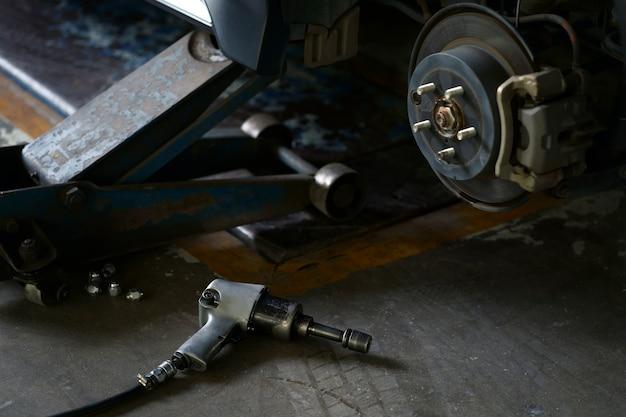 Pneumatique outil clé écrous de pneu de voiture sur le sol en béton côté voiture lift pour changer