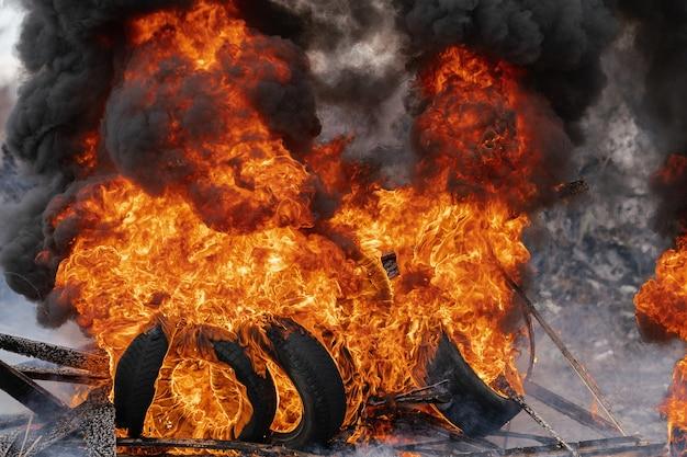 Pneus d'automobile en feu, forte flamme de feu rouge et nuages de fumée noire dans le ciel. mise au point sélective, flou d'un feu puissant.