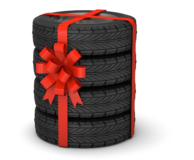 Pneus en cadeau un ensemble de quatre pneus avec des disques attachés avec un ruban cadeau rouge avec un arc isolé