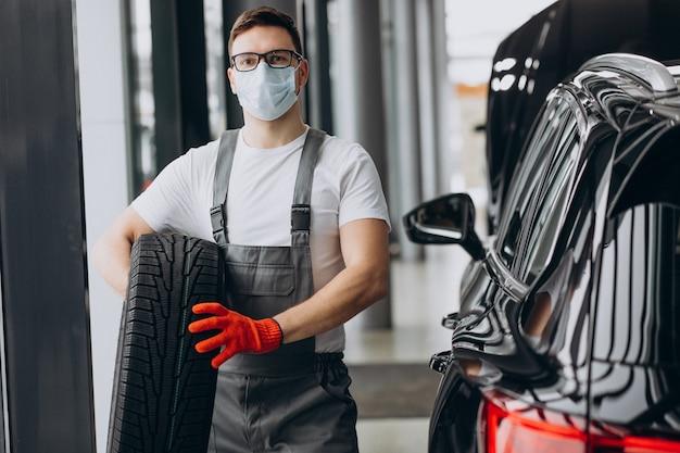 Pneus changeants de mécanicien dans un service de voiture