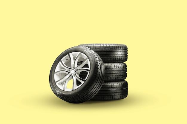 Pneus d'été et pile de roues sur fond jaune, nouvelles roues.
