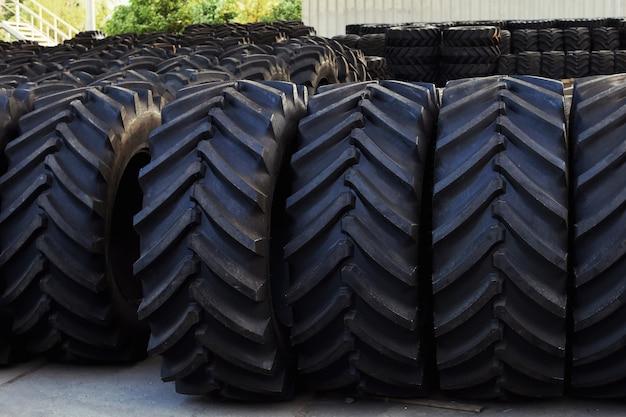 Pneus de tracteur avec un grand protecteur, dans un grand entrepôt de machines agricoles.