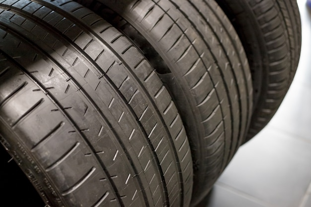 Pneus en vente dans un magasin de pneus et piles de vieux pneus usés et neufs