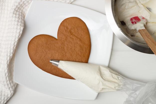 Une poche à douille avec de la crème sur une croûte en forme de cœur et un bol de crème près de la serviette, à plat.