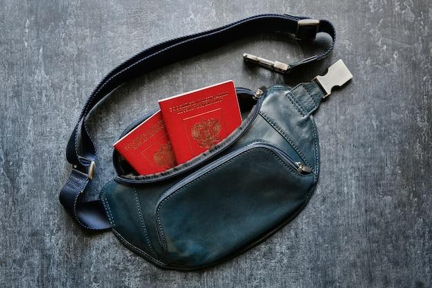 Pochette de ceinture en cuir vert avec deux passeports internationaux sur gris, vue de dessus, gros plan
