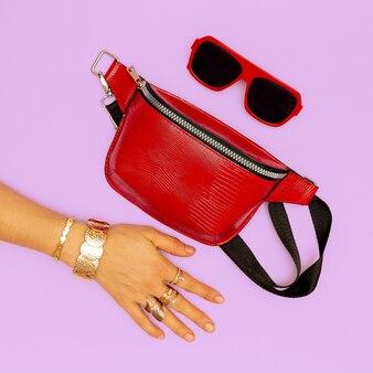 Pochette rouge tendance et bijoux en or élégants. des lunettes de soleil. tendances dame accessoires