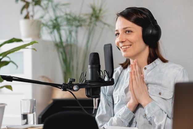 Podcaster crée du contenu une femme européenne enregistre un podcast avec un microphone et un casque caucasien