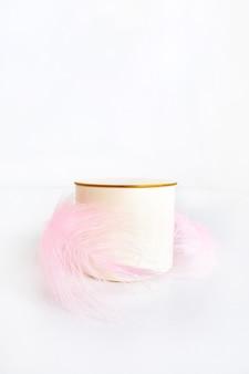 Un podium beige, un socle cylindre avec un dessus en or et une plume rose sur fond blanc comme vitrine de luxe pour votre promotion et publicité produit.