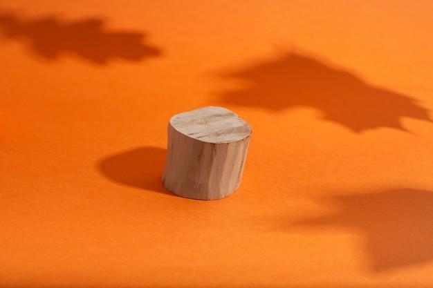 Podium en bois vide avec forme de cercle debout sur orange avec ombre de feuilles