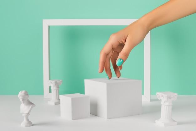 Podium de main de femme et cadre sur fond turquoise. conception d'ongle de printemps. mise en page créative de mode beauté