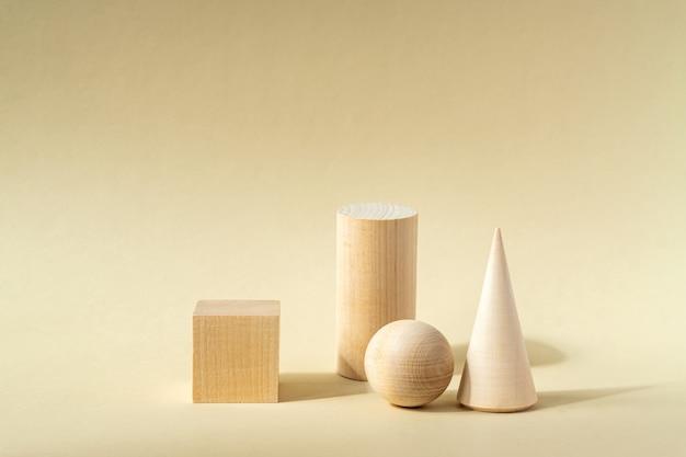 Podiums en bois clair et boule en bois sur surface beige