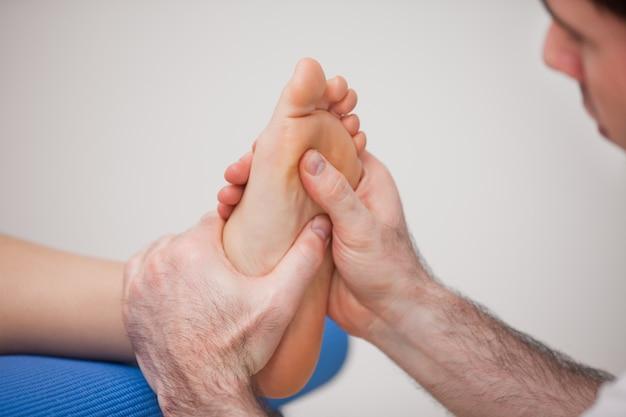 Podologue pratiquant la réflexologie sur le pied de la femme