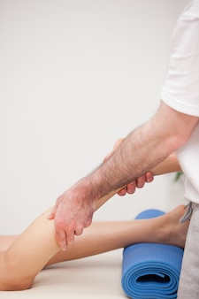 Podologue en train de masser la jambe de son patient debout