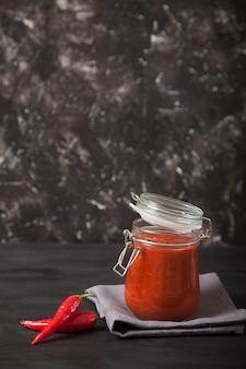 Podpava épicé de sharissa dans un bocal en verre et piment fort se dresse sur une serviette en lin. cuisine nationale traditionnelle. copiez les spas.
