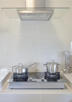 Poêle en acier inoxydable sur la cuisinière à gaz avec ustensile de cuisine moderne