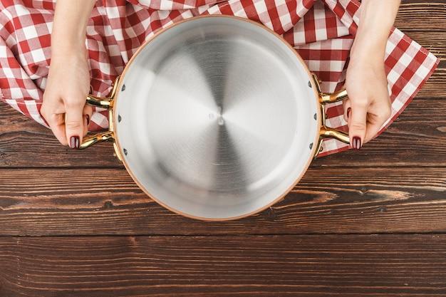 Poêle en cuivre brillant dans la main des cuisiniers sur la vue de dessus de fond en bois