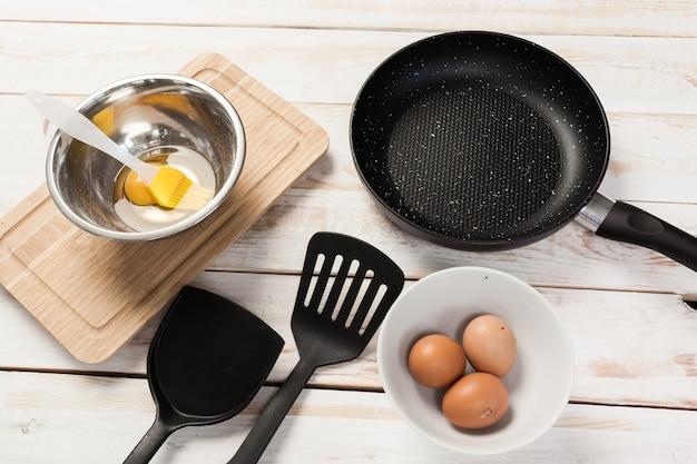 Poêle en fonte et autres ustensiles de cuisine sur table en bois, vue de dessus