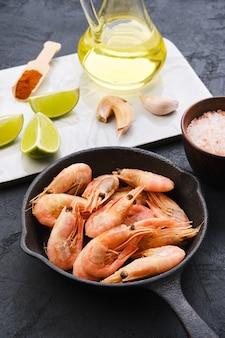 Poêle en fonte avec crevettes vapeur non pelées aux épices