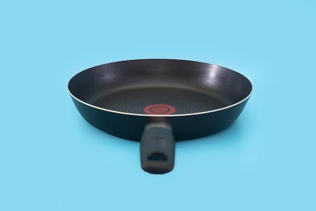 Poêle à frire antiadhésive isolée sur fond bleu.
