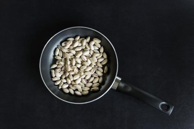 Poêle à frire aux pistaches sur fond noir.