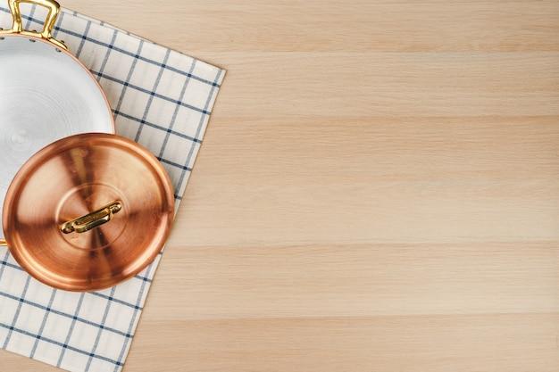 Poêle à frire en cuivre sur la vue de dessus de fond en bois