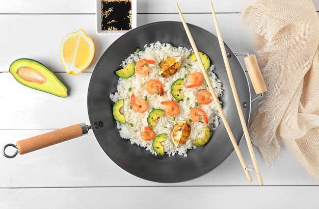 Poêle à frire avec de délicieux riz frit aux crevettes sur table