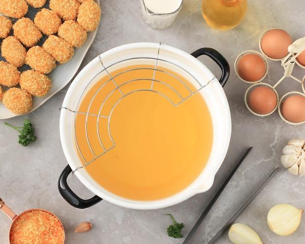Poêle à frire en émail avec vue de dessus avec grille en acier inoxydable, préparation de pépites de cuisson/arancini dans la cuisine