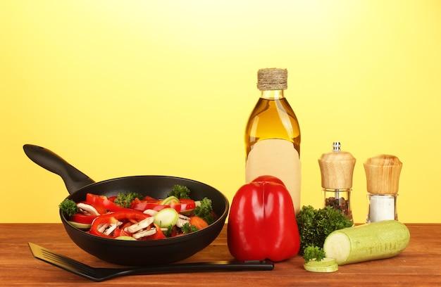 Poêle à frire avec des légumes sur fond jaune